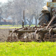 Old tractor plowing field on spring day - Stock Photo