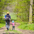 Father and son walking together on spring forest path - Stock Photo