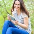 Young happy smiling woman working on pda tablet pc green outdoors - Stock Photo
