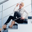 Young business fashion woman sitting on stairs - Stock Photo
