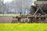 Old tractor plowing field on spring day — Stock Photo