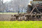 Stary ciągnik orka pola na dzień wiosny — Zdjęcie stockowe