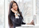 Young business woman using laptop PC relaxed near window at her office — Stock Photo