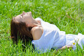 Happy young woman in short white summer dress lying on green grass — Stock Photo