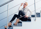 Young business fashion woman sitting on stairs — Stock Photo