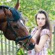 Beautiful young brunette woman holding horse — Stock Photo