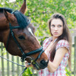 Royalty-Free Stock Photo: Beautiful young brunette woman holding horse