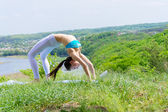 Happy young woman doing yoga on green river bank — Stock Photo
