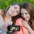 Foto de Stock  : Two happy teenage girls taking picture of themselves with mobile phone