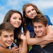 Four happy teenage friends outdoors — Stock Photo