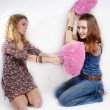 Portrait of two beautiful young women playing with two pink hearts on white background — Stock Photo