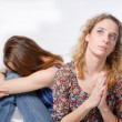 Two beautiful young women comforting each other & praying on white background — Stock Photo #26033429