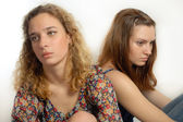 Two beautiful young women looking away sad on white background — Stock Photo