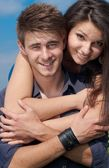 Happy teenage couple embracing over blue sky background — Stock Photo