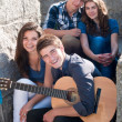 Four happy teenage friends and guitar — Stock Photo