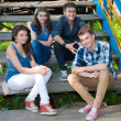 Four happy teenage friends sitting on stairs — Stock Photo #26129073