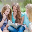 Three teen girl friends reading school book — Stock Photo