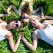 Three happy teen girls lying on green grass and holding hands — Stock Photo #26131305