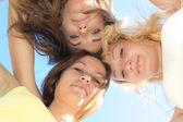 Três meninas adolescentes felizes olhando para baixo, contra o céu azul — Foto Stock