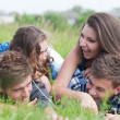 Four happy teenage friends lying together on green grass outdoors — Stock Photo #26964381
