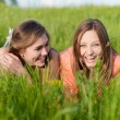 Two Teen Girl Friends Laughing  in green grass — Stok fotoğraf