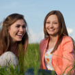 Stock Photo: Two Teen Girl Friends Laughing in green grass