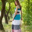 Young happy woman wearing long dress walking in green park — Stok fotoğraf