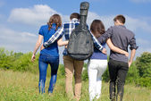 Four happy teenage friends walking together outdoors — Stock Photo
