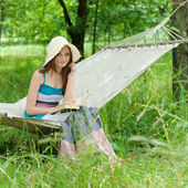 Happy young woman reading in hammock in green park outdoors — Stock Photo