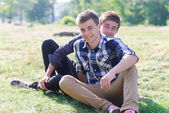 Two young men sitting together on green grass — Stock Photo