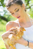 Happy young woman taking care of chicken — Fotografia Stock