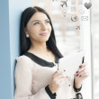 Smiling young business woman using tablet PC while standing relaxed near window at her office — Stock Photo #27445507