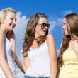 Three happy teen girls embracing against blue sky — Stock Photo #27663403