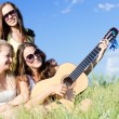 Three happy teen girls singing and playing guitar against blue sky — Stock Photo