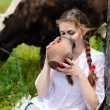 Young happy womman drinking fresh milk near cows in countryside — Stock Photo
