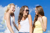 Three happy teen girls embracing against blue sky — Stock Photo