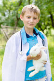 Young happy boy embracing little rabbit outdoors — Stock Photo