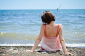 Young woman sitting on sand and looking to a sea — Stock Photo