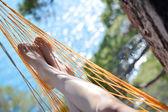Vista de pernas de mulher suave agradável deitado na rede no litoral — Fotografia Stock