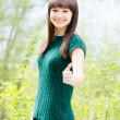 Beautiful young woman in knitted green blouse showing thumbs up — Stock Photo