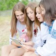 Four happy teen girl friends and tablet computer — Stock Photo