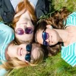Three happy teen girls lying on green grass in sunglasses — Stock Photo #28383105
