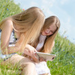 Stock Photo: Happy smiling teen girls and tablet computer