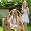 Two young women in country yard with spinning wheel and rock chair — Stock Photo #28383971