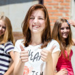 Three young happy teenage girls showing thumb up — Stock Photo #28384891