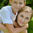 Teenage sister and little brother embracing outdoors — Stock Photo