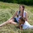 Teenage sister and little brother sitting on hay — Stock Photo #28385159