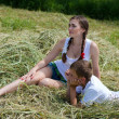 Teenage sister and little brother sitting on hay — Stock Photo