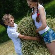 Teenage sister and little brother holding velour grass or hay — Stock Photo