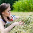 Young beautiful woman lying on hay one summer day — Stock Photo